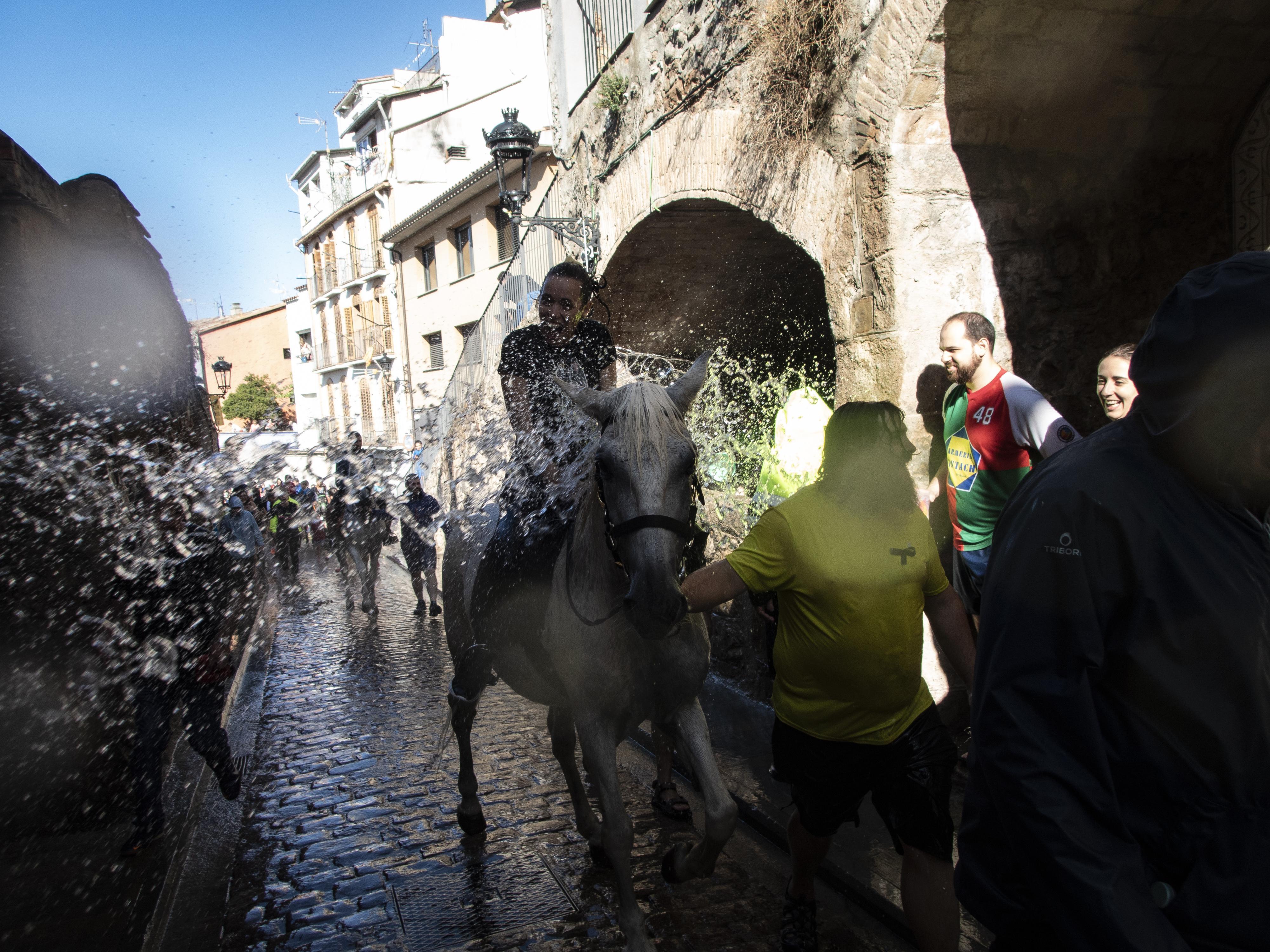Cavalls i cavallistes remullats al seu pas pel safareig de la Pietat. FOTO: Anna E. Puig